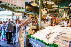 Customers at Pike Place Fish Company in Seattle, Washington. This market, opened in 1930, is known for their open air fish market style.
