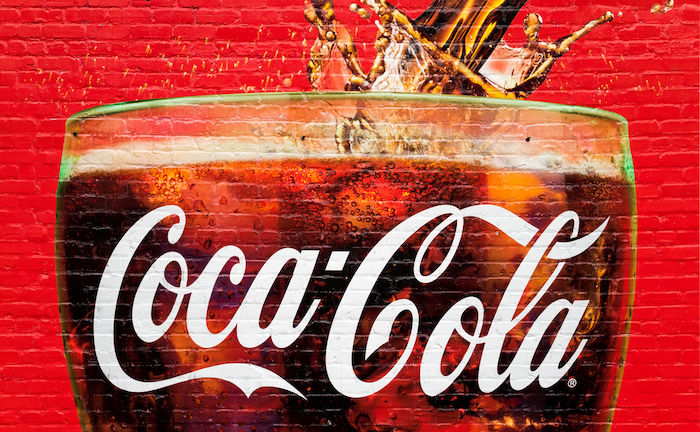 Atlanta, GA, - A glass full of Coca Cola painted in a old wall in Atlanta. The city is the home of Coca Cola. Photo via Shutterstock.