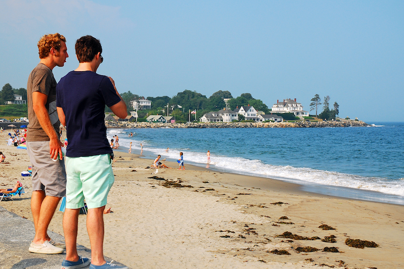 Rye, NH, USA July 15 Two young men taken in the ocean view along a seawall at Jenness Beach State Park in  Rye, New Hampshire. Photo by Shutterstock.