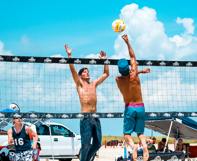 Men play volleyball on the beach. Photo by Shutterstock.