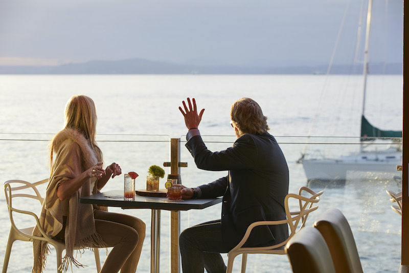 Couple dining on the deck at the Edgewater hotel in Seattle. Photo via the hotel.