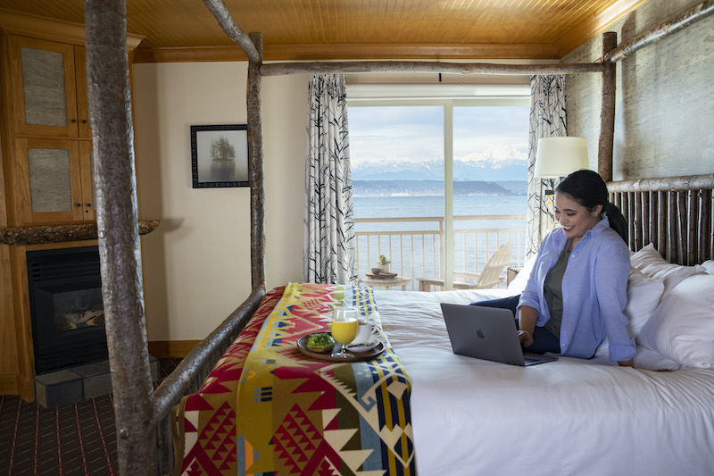 Woman working in a guest room at the Edgewater hotel in Seattle. Photo via the hotel.